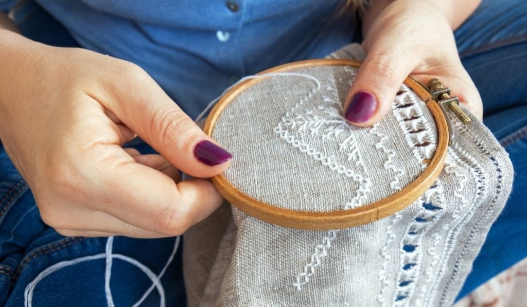 woman hands doing open embroidery